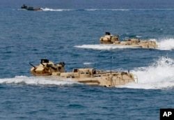 FILE - U.S. Navy amphibious assault vehicles with Philippine and U.S. troops on board are seen during joint exercises near a beach facing one of the contested islands in the South China Sea known as the Scarborough Shoal in the West Philippine Sea.