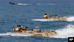 FILE - U.S. Navy amphibious assault vehicles with Philippine and U.S. troops on board are seen during joint exercises near a beach facing one of the contested islands in the South China Sea known as the Scarborough Shoal, April 21, 2015.