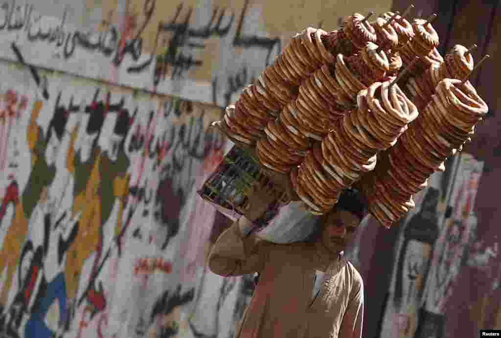 Seorang penjual roti berjalan di depan sebuah tulisan yang mengecam Presiden Mesir, Mohamed Morsi dekat Lapangan Tahrir di Kairo.