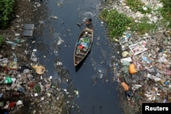 FILE - A man on a boat collects plastic materials from dirty water in Dhaka, Bangladesh, April 17, 2019.