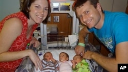 A photo provided by Texas Children's Hospital shows Lauren and David Perkins with three of their six children born prematurely in April