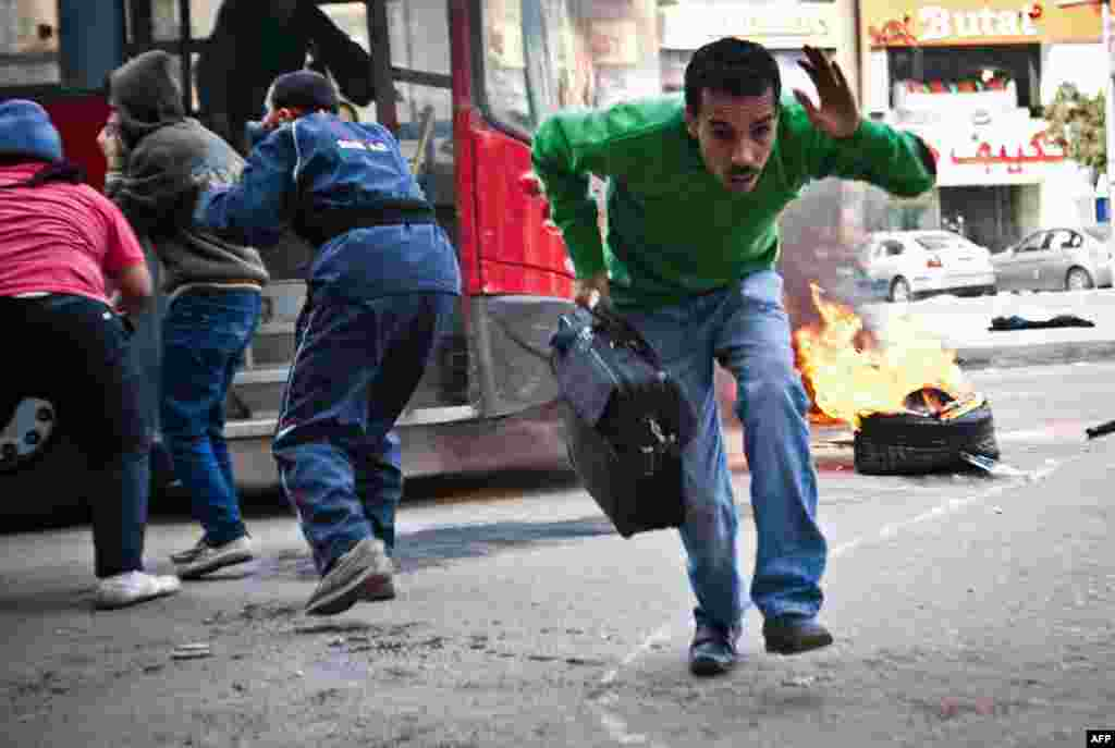 An Egyptian civilian runs out of a public bus after it was caught up in clashes between supporters of Egypt's deposed president Mohamed Morsi and police in the northeastern part of Cairo's Nasr City district.