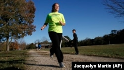 """Grace Brown, 14, poses for a portrait while jogging at the park where she does her jogging workouts for her """"online PE"""" class, in Alexandria, Va., Friday, Nov. 1, 2019. (AP Photo/Jacquelyn Martin)"""
