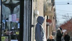 A man stand outside a small store in Camden, New Jersey, which has the highest poverty rate in the nation.