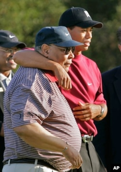 This Dec. 12, 2004 file photo shows Tiger Woods, right, hugging his father, Earl, after winning the Target World Challenge in Thousand Oaks, Calif. After Tiger Woods' Masters victory in 1997, there was widespread speculation that his rise to prominence wo