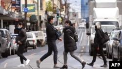 호주 최대 도시 시드니에서 신종 코로나바이러스 방역 관련 봉쇄를 해제한 11일 수도 멜버른 시민들이 마스크를 쓴 채 길을 건너고 있다.