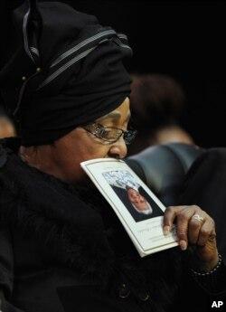 Winnie Madikizela-Mandela, Nelson Mandela's former wife, holds up the service program while attending former South African President Nelson Mandela's funeral service in Qunu, South Africa, Dec. 15, 2013.