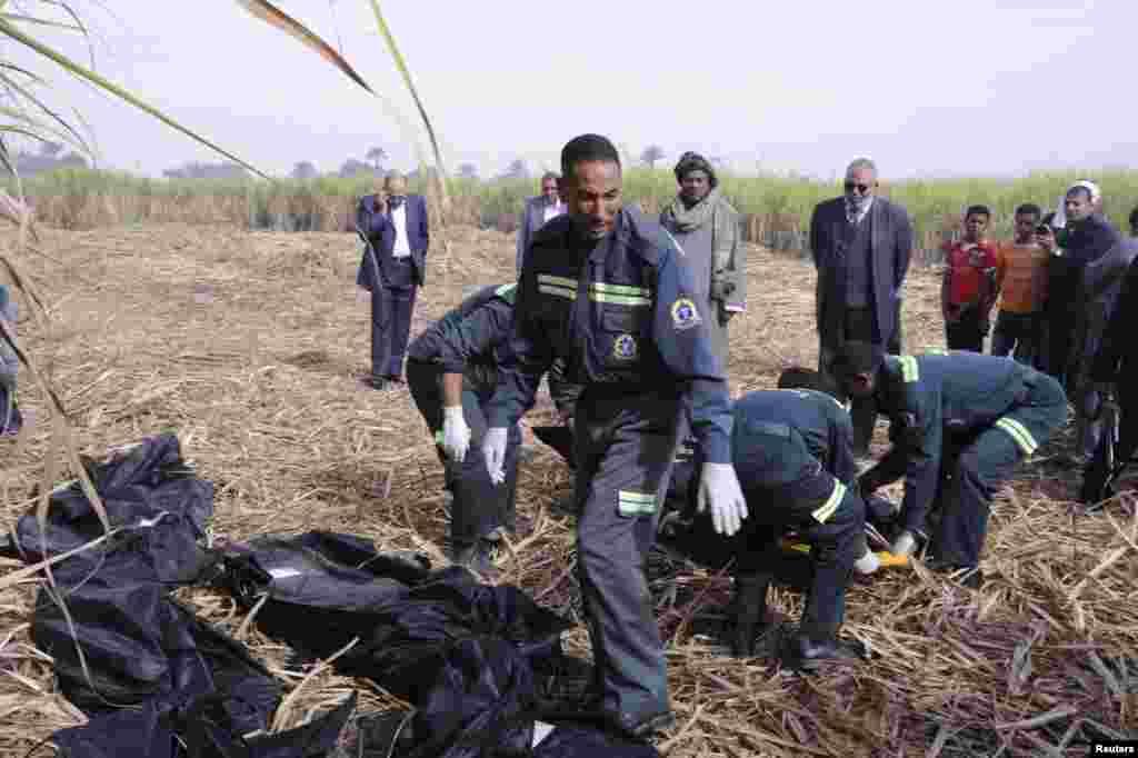 Polisi dan petugas penyelamatan mengangkat jenazah para turis yang tewas dalam ledakan balon udara di Luxor, Mesir (26/2).