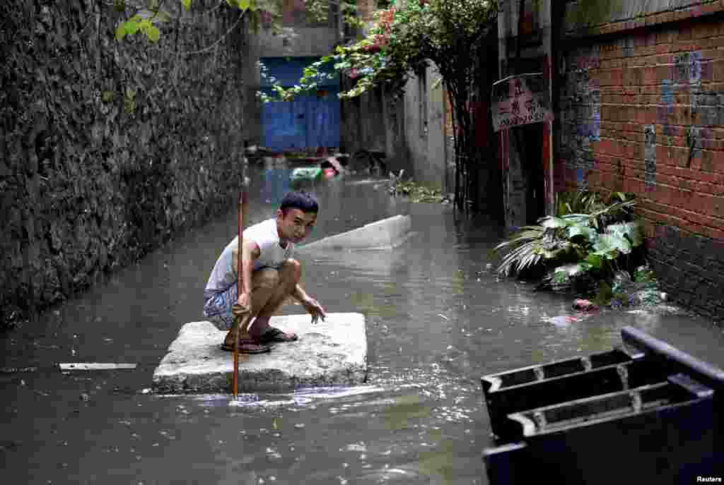 A man travels down a flooded alley on a styrofoam board after heavy rainfall in Liuzhou, Guangxi Zhuang Autonomous Region, China.