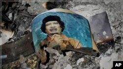 រូបថតរបស់មេដឹកនាំលីប៊ី Moammar Gadhafi ដែលត្រូវបានបណ្តេញចេញពីតំណែង ត្រូវគេឃើញនៅក្នុងគំនរផេះ នៅទីប្រជុំជននៃទីក្រុងស៊ឺត (Sirte) នៃប្រទេសលីប៊ី នៅថ្ងៃទី១២ ខែតុលា ឆ្នាំ២០១១។