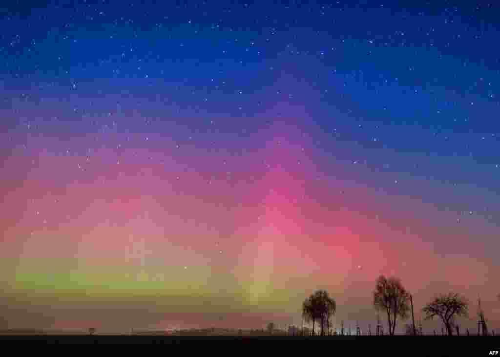 Cahaya terang warna-warni (Aurora borealis) menghiasi langit malam hari di kota Lietzen, dekat Brandenburg, Jerman.