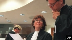 Prosecutor, Justice Louise Arbour, centre, talks to Mark Harmon, right, Senior Trial Attorney, shortly before the beginning of the hearing at the International Criminal Tribunal for former Jugoslavia in The Hague, file photo.