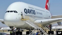 In this July 6, 2020, file photo, a Qantas Airbus A380 arrives in Victorville, Calif. Qantas said that once a virus vaccine becomes widely available, the carrier will likely require it before passengers can travel abroad or land in Australia. (AP Photo/Matt Hartman, File)
