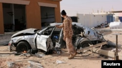 A Libyan soldier allied with the self-proclaimed Tripoli government stands next to a damaged vehicle at the scene of an air attack in Ben Jawad, Feb. 2, 2015.
