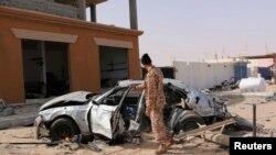 Un soldat libyen se tient devant un voiture brûlée à Ben Jawad le 2 fébrier 2015.