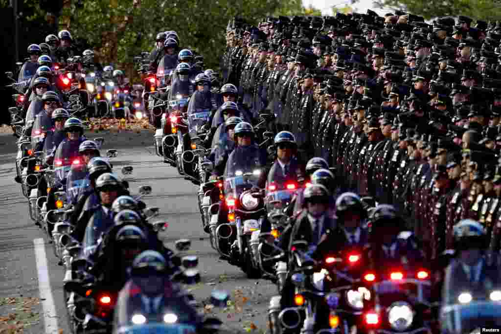 A procession of police motorcycles pass officers lining the street at the funeral service for New York City Police Department (NYPD) officer Brian Mulkeen at the Sacred Heart Church in Monroe, New York.