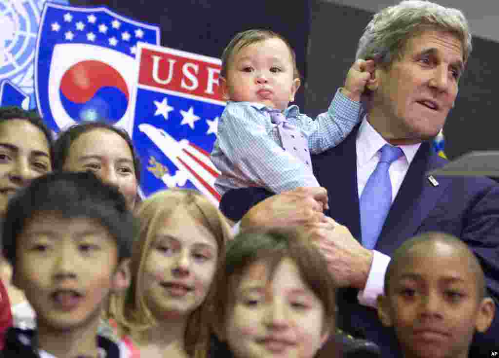 U.S. Secretary of State John Kerry, right, holds 8-month-old Andrew Belz as he poses for photos with the children of U.S. troops and U.S. Embassy personnel at Collier Field House at Yongsan Garrison in Seoul, South Korea.
