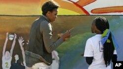 خانمی یهکهمی ئهمهریکا میشێێل ئۆباما لهسهر دیواری کلینیکێـکی نهخۆشی ئهیدز له گابۆرۆنی پایتهختی بۆتسوانا وێنه دهکێشێت، ههینی 24 ی شهشی 2011