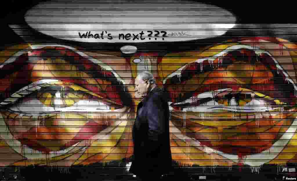 یک مرد از برابر گرافیتی در پیاده روی آتن میگذرد. ولفگانگ شابل، وزیر دارایی آلمان، روز چهارشنبه ۶ اسفندماه ۱۳۹۳ (۲۵ فوريه ۲۰۱۵) گفت تمديد طرح نجات یونان به مدت چهار ماه تصمیم آسانی برای وزرای دارایی منطقه یورو نبوده است.