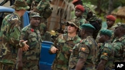 FILE - U.S. Army special forces Master Sergeant speaks with troops from the Central African Republic and Uganda, where U.S. special forces have paired up with local troops and Ugandan soldiers to seek out Joseph Kony's LRA, in Obo, Uganda.