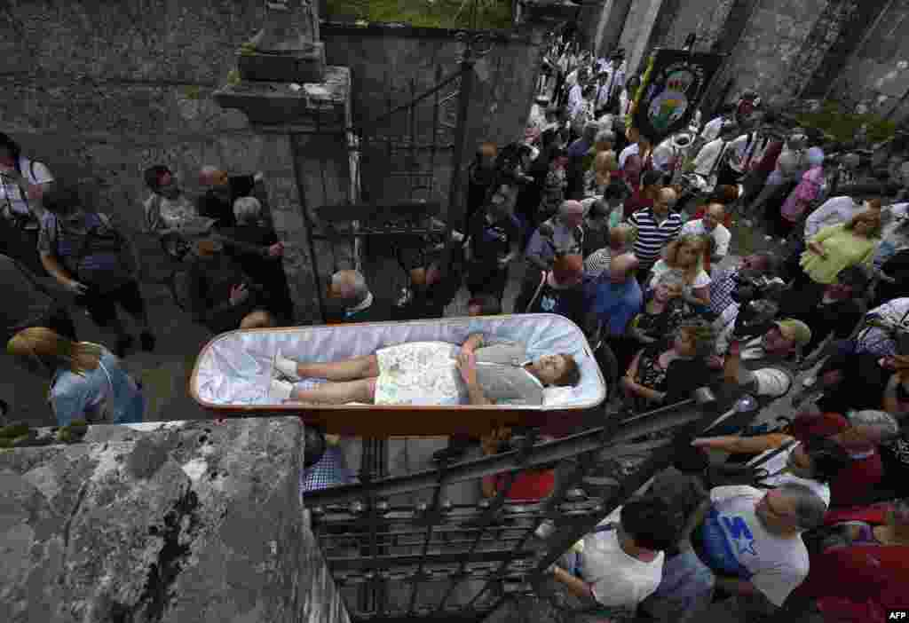 "A woman is carried in a coffin by relatives during the annual ""Procession of the Shrouds"" to celebrate Saint Martha ""the Saint of resurrection"" in the village of Santa Marta de Ribarteme, northwestern Spain. People who have escaped death lie in caskets and are carried in procession by relatives in a thankful gesture for being kept alive."