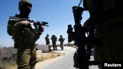 Tentara Israel berpatroli dalam operasi pencarian riga remaja yang hilang di kota Hebron, Tepi Barat (18/6).
