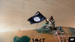FILE - A fighter of the Islamic State group waving their flag.