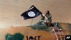 Un combatiente del Estado Islámico ondea una bandera dentro de un avión sirio capturado en Raqqa.
