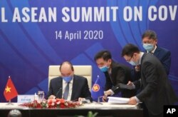 Vietnamese Prime Minister Nguyen Xuan Phuc, left, and his staff prepare documents ahead of the Special ASEAN summit on COVID-19 in Hanoi, Vietnam Tuesday, April 14, 2020.