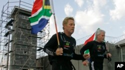 FILE - South African runner Braam Malherbe, left, and Dawid Grier run past the prison where former South African President Nelson Mandela spent most of the 27 years that he was jailed, during his 90th birthday celebration on Robben Island, South Africa, July 18, 2008.