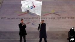 Chen Jining, mayor of Beijing waves the Paralympic flag after receiving it from Andrew Parsons, President of the International Paralympic Committee, left, at the closing ceremony of the 2018 Winter Paralympics in Pyeongchang, South Korea, March 18, 2018.