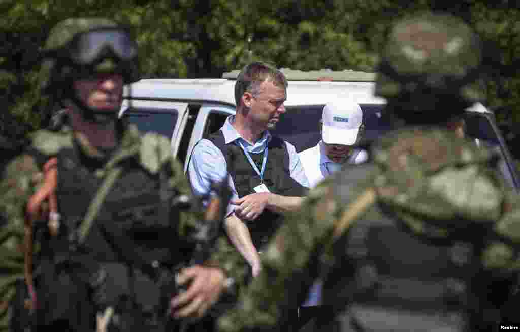 Alexander Hug (center), deputy head of OSCE, Europe's monitoring mission in Ukraine, stands next to armed pro-Russian separatists as the convoy makes its way to the MH17 crash site outside Donetsk, July 30, 2014.