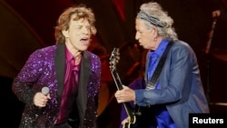 "FILE - British veteran rockers The Rolling Stones lead singer Mick Jagger sings next to band member Keith Richards, as they open their North American ""Zip Code"" tour in San Diego, California, May 24, 2015."