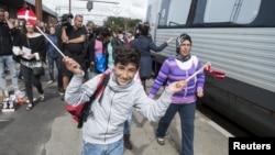 Agitant des drapelets danois, un jeune homme débarque d'un train, avec d'autres migrants, principalement de la Syrie, à la station de Padborg,10 septembre 2015.