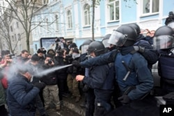 Police use tear gas as they clash with supporters of former Georgian president Mikheil Saakashvili in Kyiv, Ukraine, Dec. 5, 2017.
