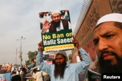 FILE - A supporter of Islamic charity organization Jamaat-ud-Dawa (JuD) carries a sign during a protest demonstration in Karachi.