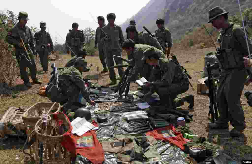 Rebel soldiers of the Myanmar National Democratic Alliance Army (MNDAA) examine weapons and ammunition at a military base in Kokang region March 10, 2015. Fighting broke out last month between Myanmar's army and MNDAA, which groups remnants of the Communist Party of Burma, a powerful Chinese-backed guerrilla force that battled Myanmar's government before splintering in 1989. Picture taken March 10, 2015.