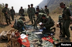 Rebel soldiers of the Myanmar National Democratic Alliance Army (MNDAA) examine weapons and ammunition at a military base in Kokang region, March 10, 2015.