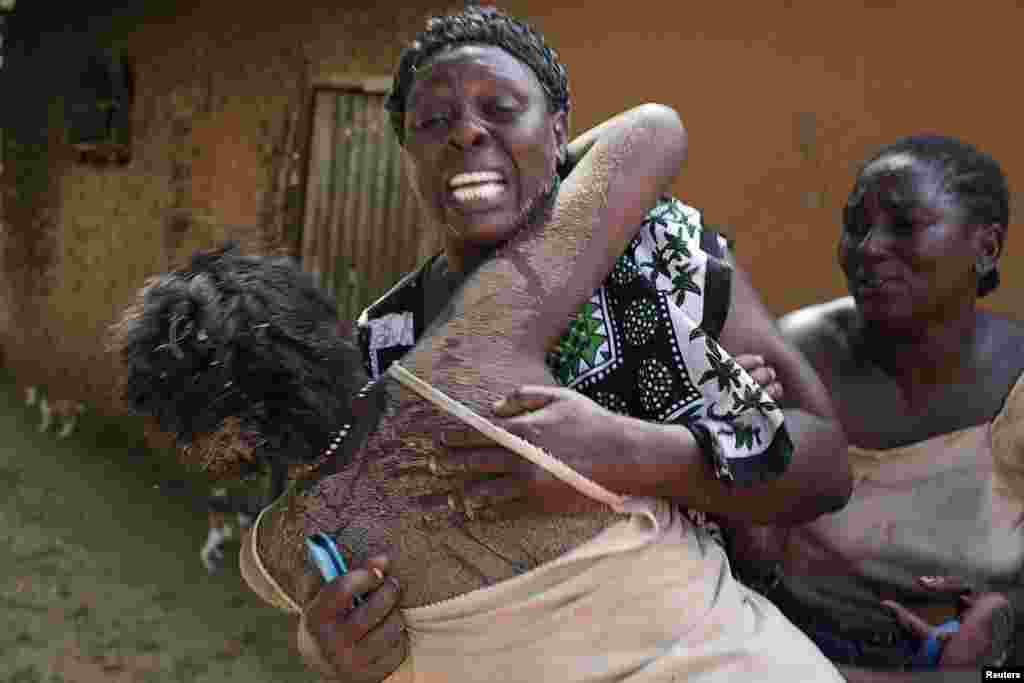 Women embrace in grief after an attack in Kibusu village in the Tana Delta region of the Kenya, January 10, 2013.