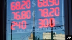 FILE - A sign shows currency exchange rates in Moscow, Russia, Aug. 21, 2015. Oil prices and economic sanctions have hit the country hard.