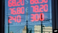 FILE - The building of the Russian Foreign Ministry, center rear, is reflected in a sign showing currency exchange rates in Moscow, Russia.