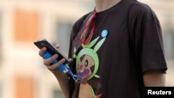 A young man's T-shirt gives him away — he's a Pokemon fan.