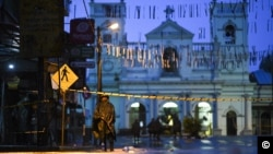Sri Lankan soldiers stand guard in the rain at St. Anthony's Shrine in Colombo, April 25, 2019. Sri Lanka's Catholic church suspended all public services over security fears, and authorities urged Muslims to pray at home Friday rather than attend a mosque.