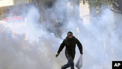 A protester runs from tear gas during clashes with security forces near the Interior Ministry in Cairo, February 5, 2012.