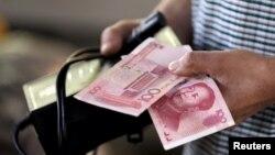 12일 중국 베이징의 시장에서 고객이 지갑에서 위안화 지폐를 꺼내고 있다.