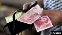 중국 베이징의 시장에서 한 고객이 지갑에서 위안화 지폐를 꺼내고 있다. (자료사진)