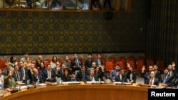 FILE - Ambassadors to the U.N. vote during a United Nations Security Council meeting on North Korea in New York City, Sept. 11, 2017.