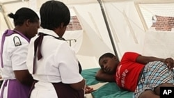 FILE: A woman is attended to after suffering from a suspected case of typhoid at a local hospital in Harare, January 31, 2012.