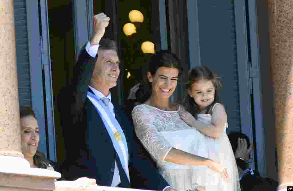 Accompanied by First Lady Juliana Awada and their daughter Antonia, Argentina's President Mauricio Macri greets the crowd from the balcony of the government house in Buenos Aires.