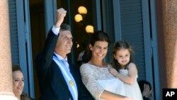 Ditemani istrinya Juliana Awada dan anaknya Antonia, Presiden Argentina yang baru dilantik menyapa orang-orang dari balkoni rumah dinas di Buenos Aires, Argentina, Kamis, 10 Desember 2015.